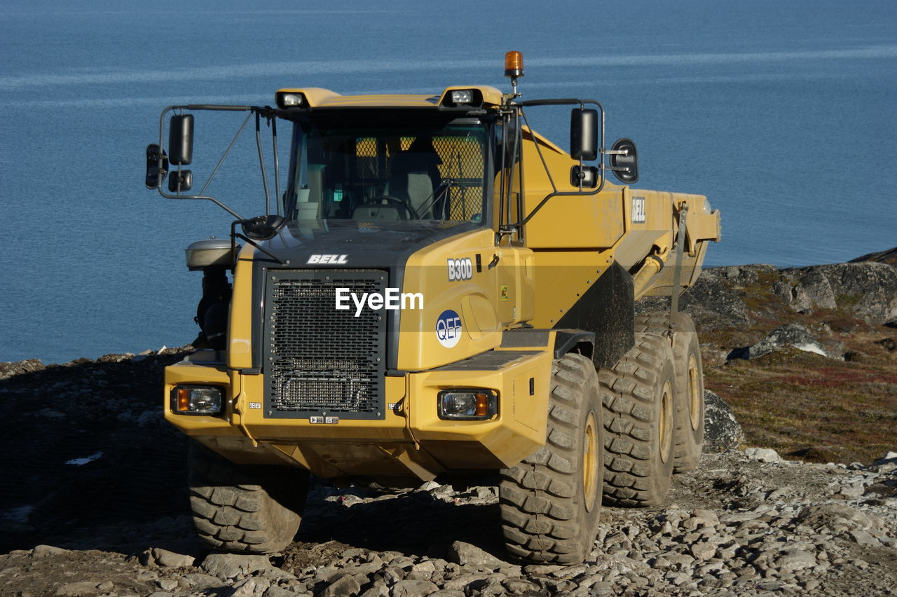 transportation, mode of transportation, land vehicle, yellow, bulldozer, construction industry, construction site, nature, construction machinery, no people, construction vehicle, day, machinery, road, land, earth mover, construction equipment, outdoors, industry, sunlight