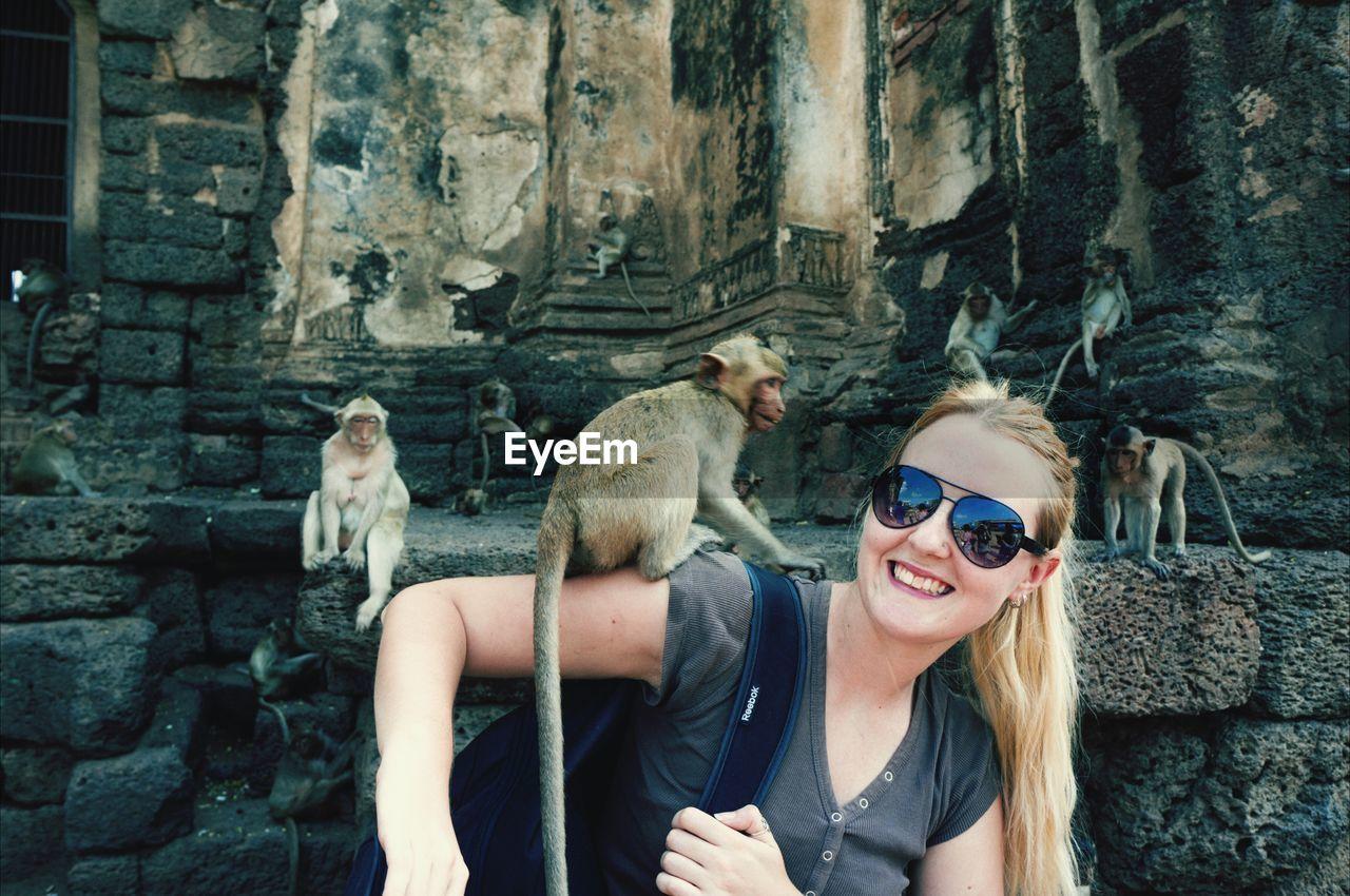 Smiling blond woman holding monkey on shoulder