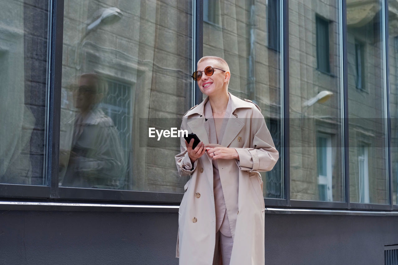 Smiling businesswoman using mobile while standing against building