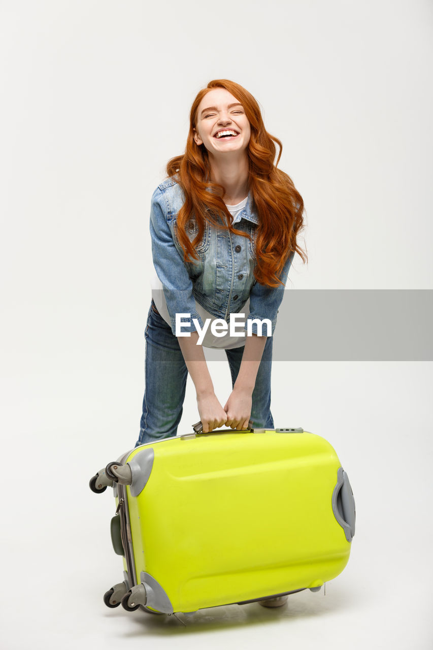 Young woman lifting suitcase while standing against white background
