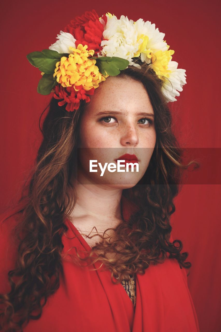 Portrait of young woman wearing floral crown against red background
