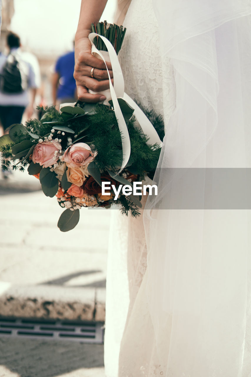 Midsection of bride holding bouquet at wedding ceremony