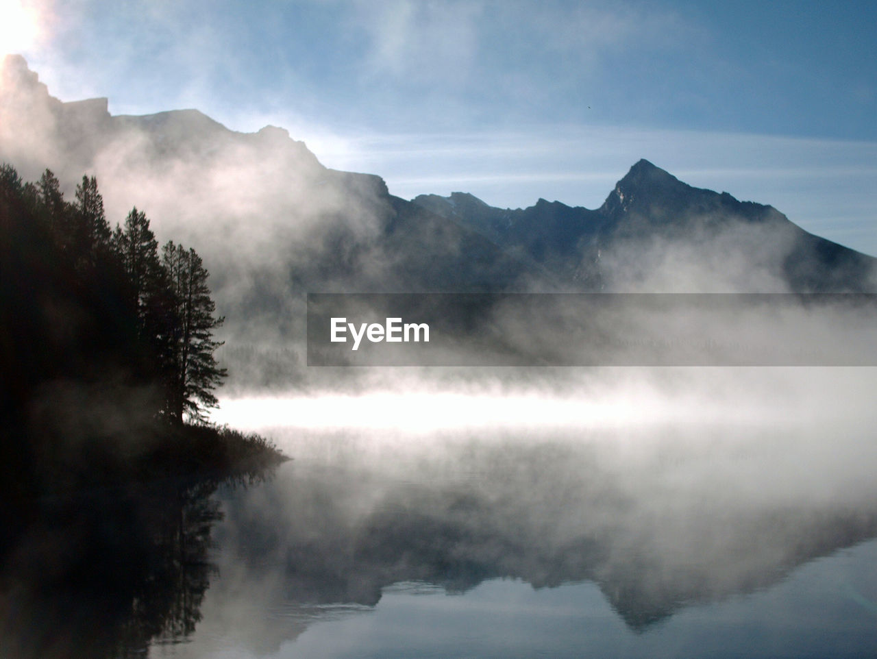 Reflection Of Mountains And Trees In Lake During Foggy Weather