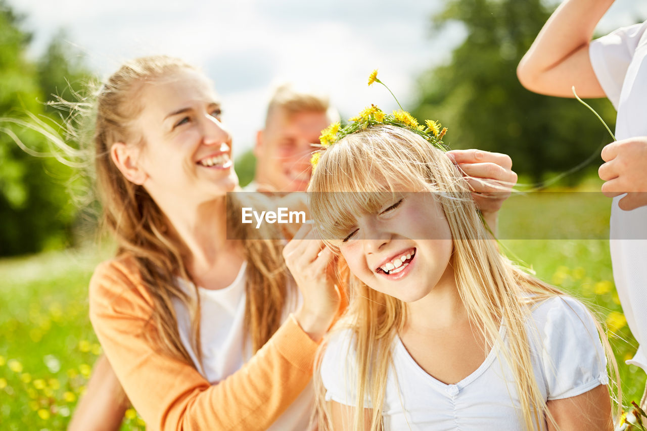 Mother Placing Flowers On Cheerful Daughter Head At Park