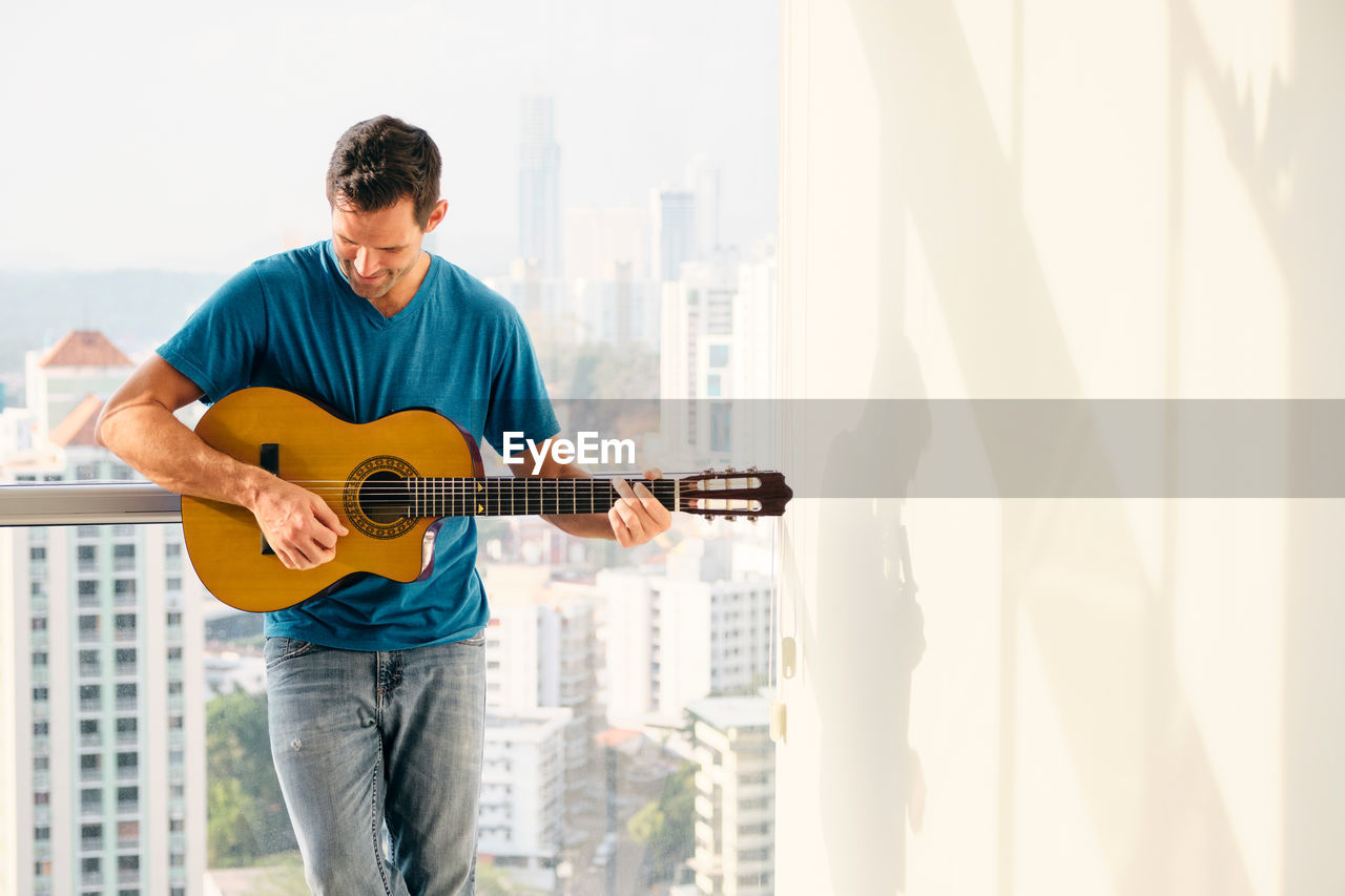 Man playing guitar standing at home