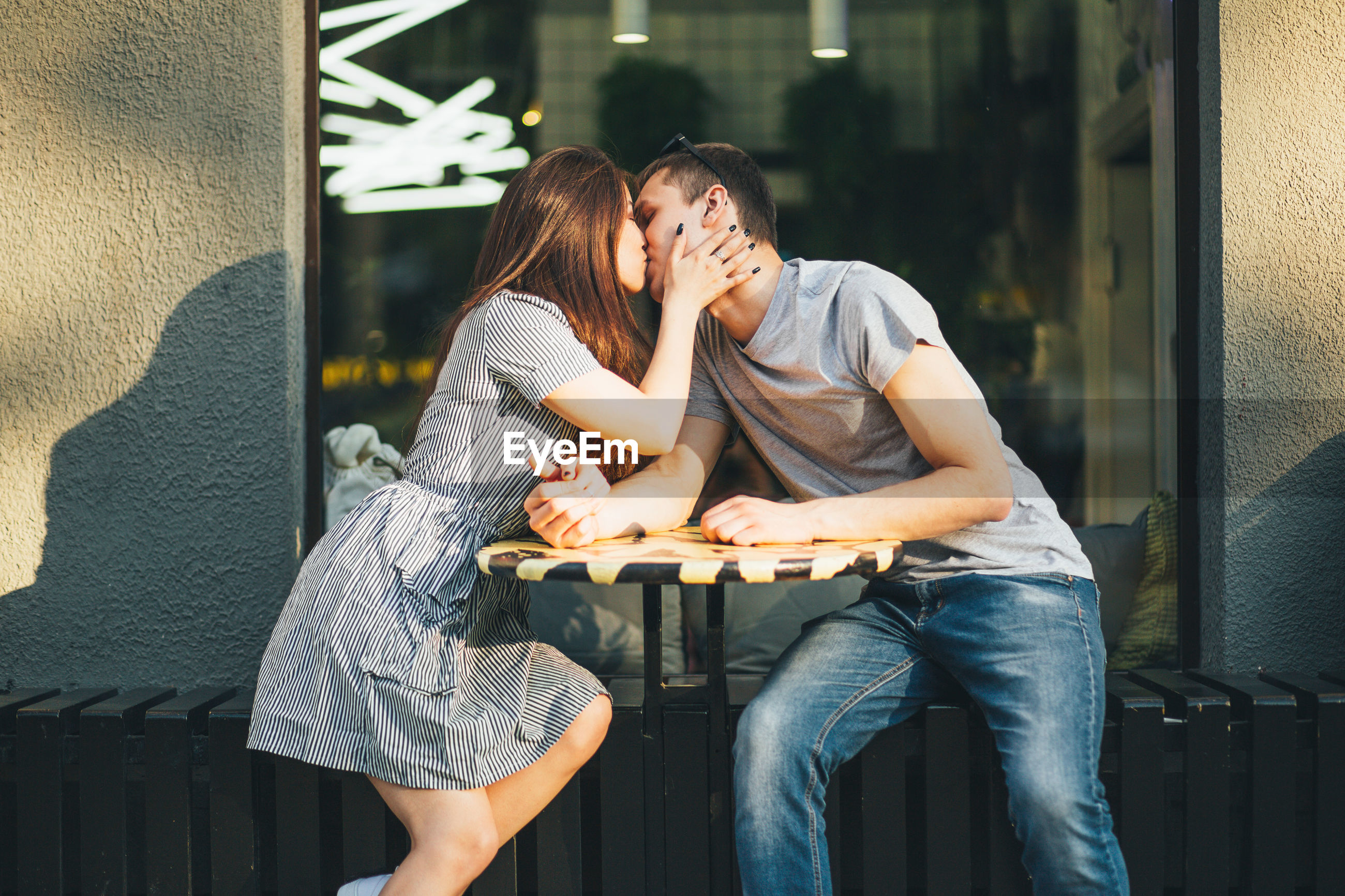 Young couple kissing while sitting at sidewalk cafe