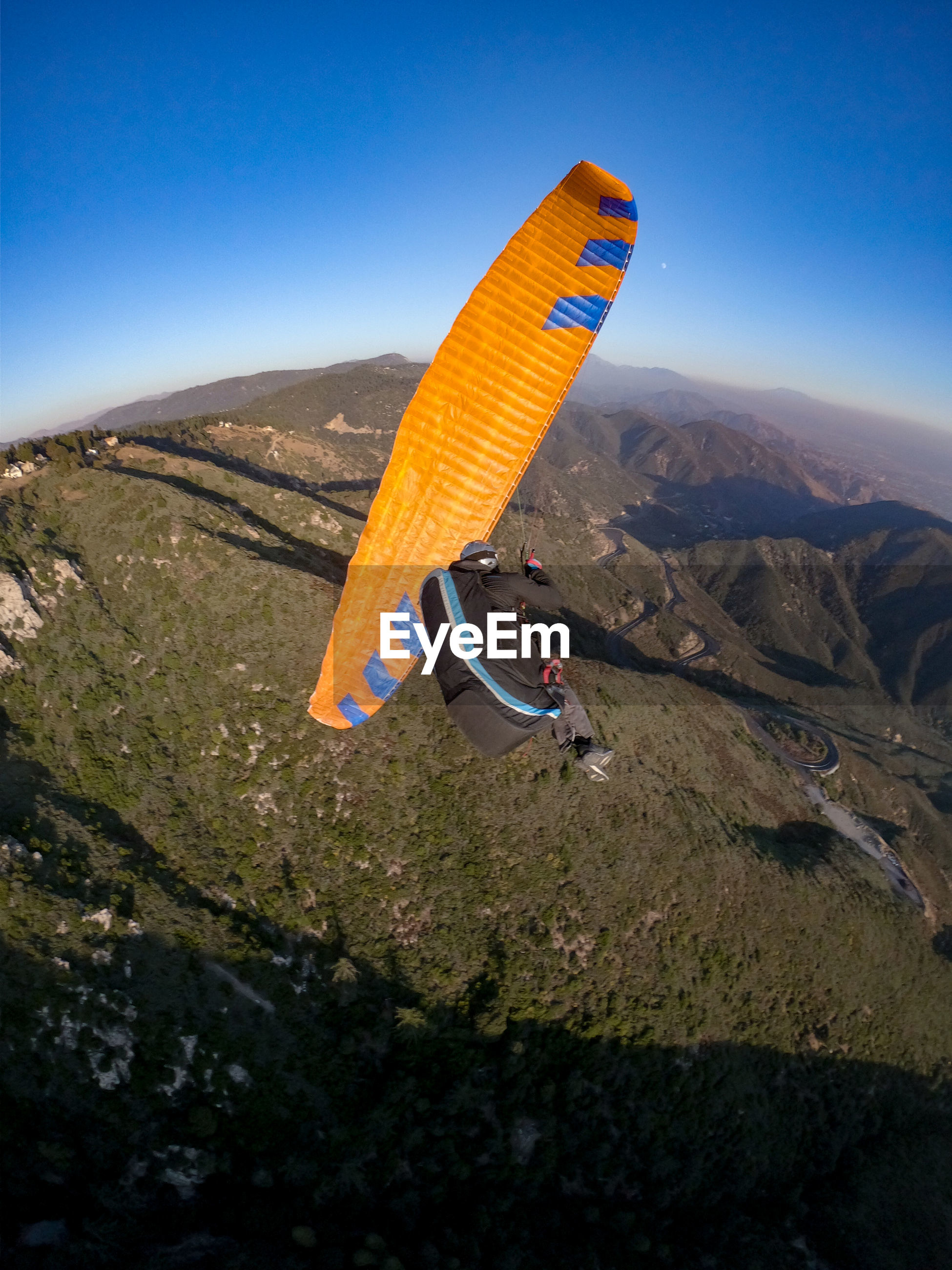 HIGH ANGLE VIEW OF KITE FLYING OVER MOUNTAIN