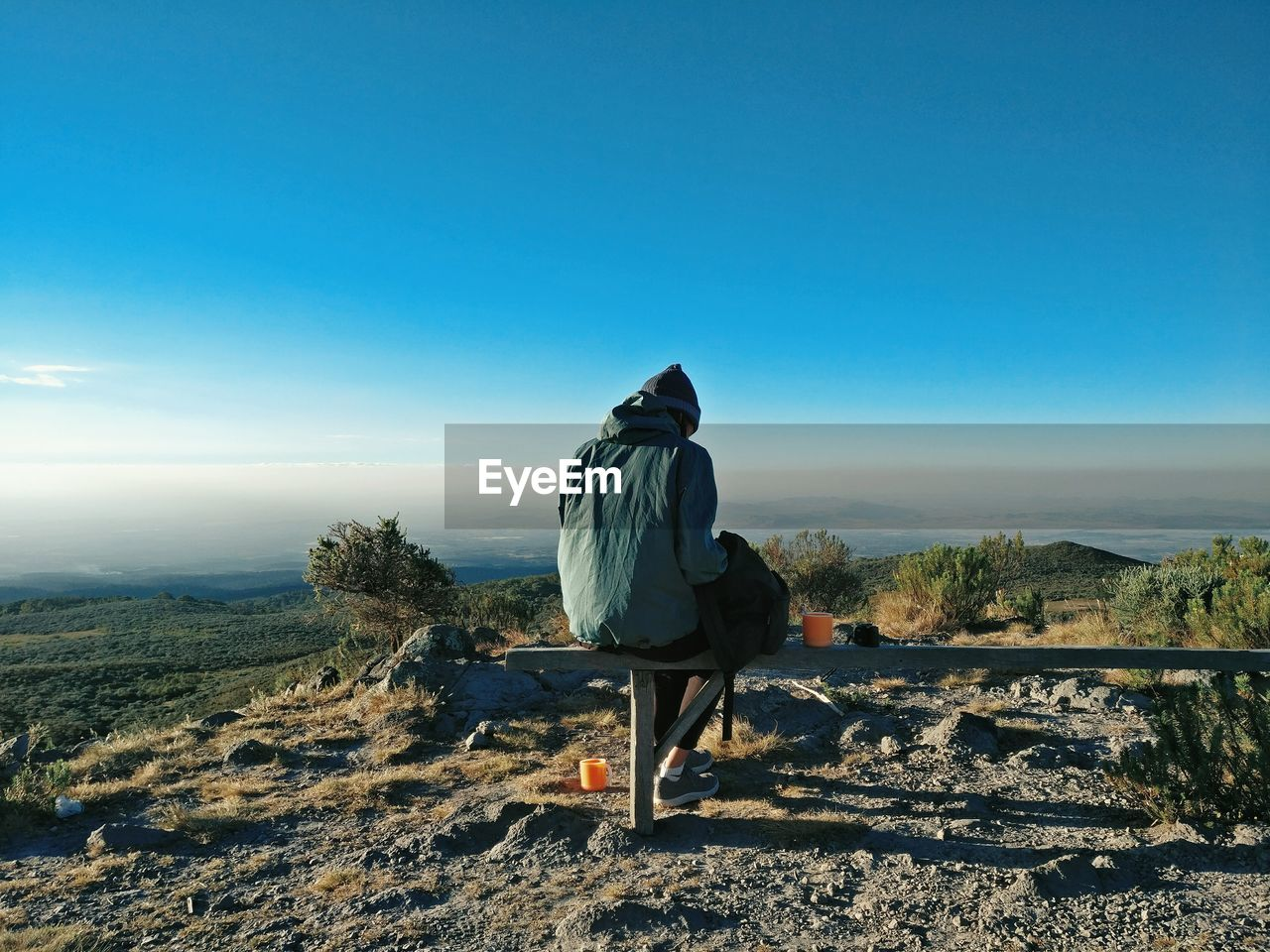sky, rear view, real people, one person, nature, full length, men, leisure activity, scenics - nature, lifestyles, copy space, tranquility, day, casual clothing, sitting, mountain, tranquil scene, landscape, environment, looking at view, outdoors, warm clothing