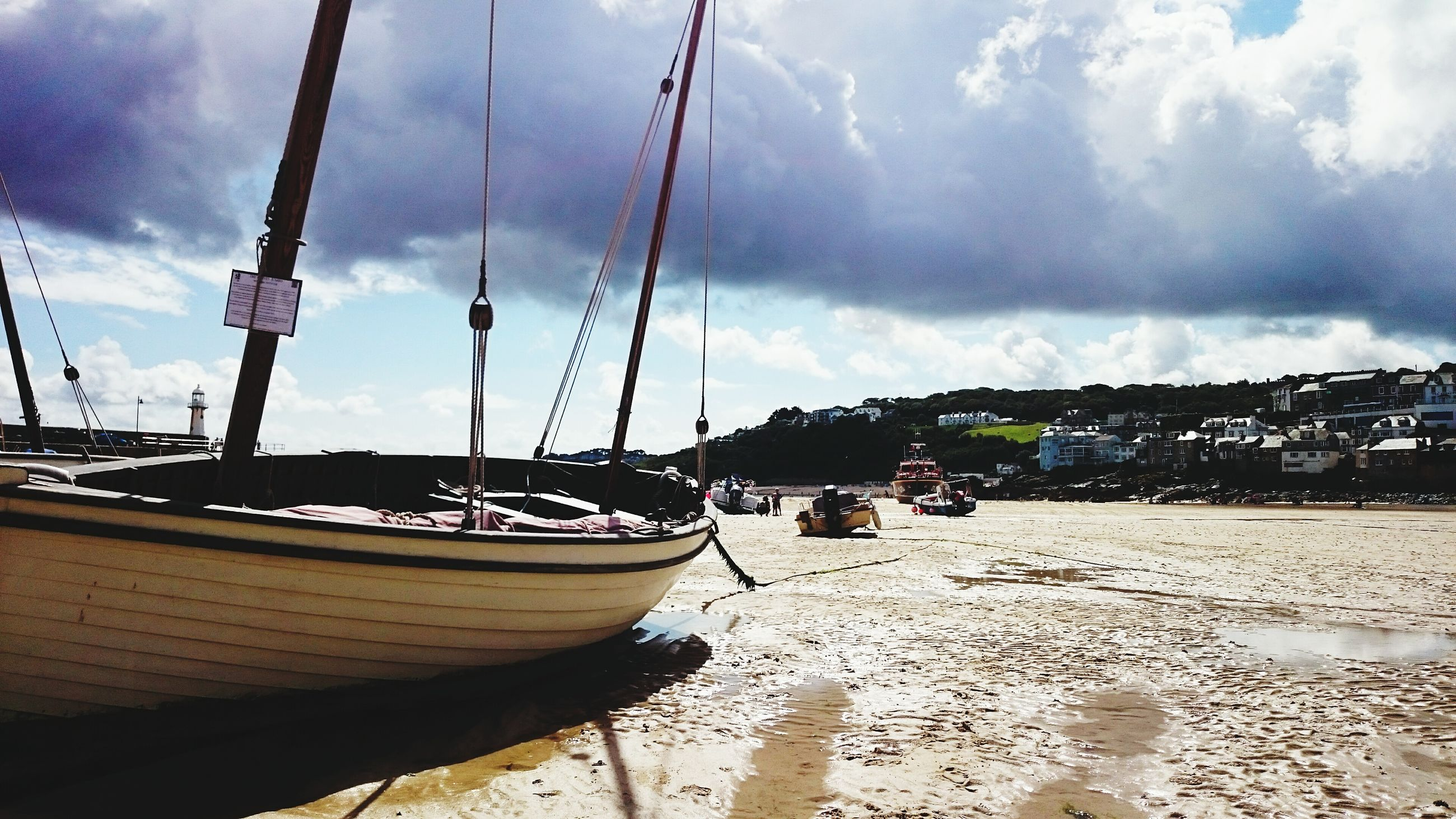 Boats moored at beach against cloudy sky