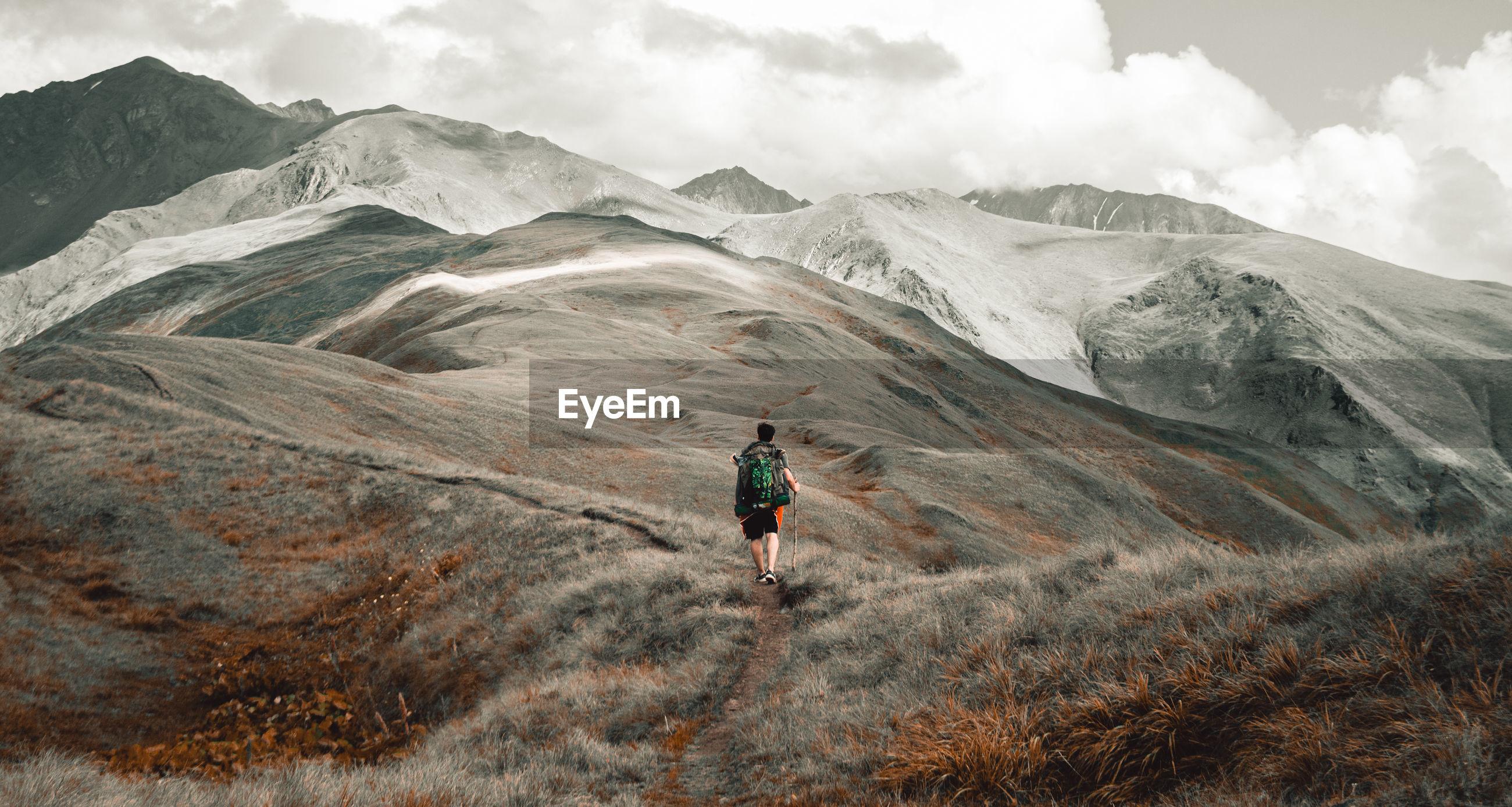 Full length of man walking on mountains against sky