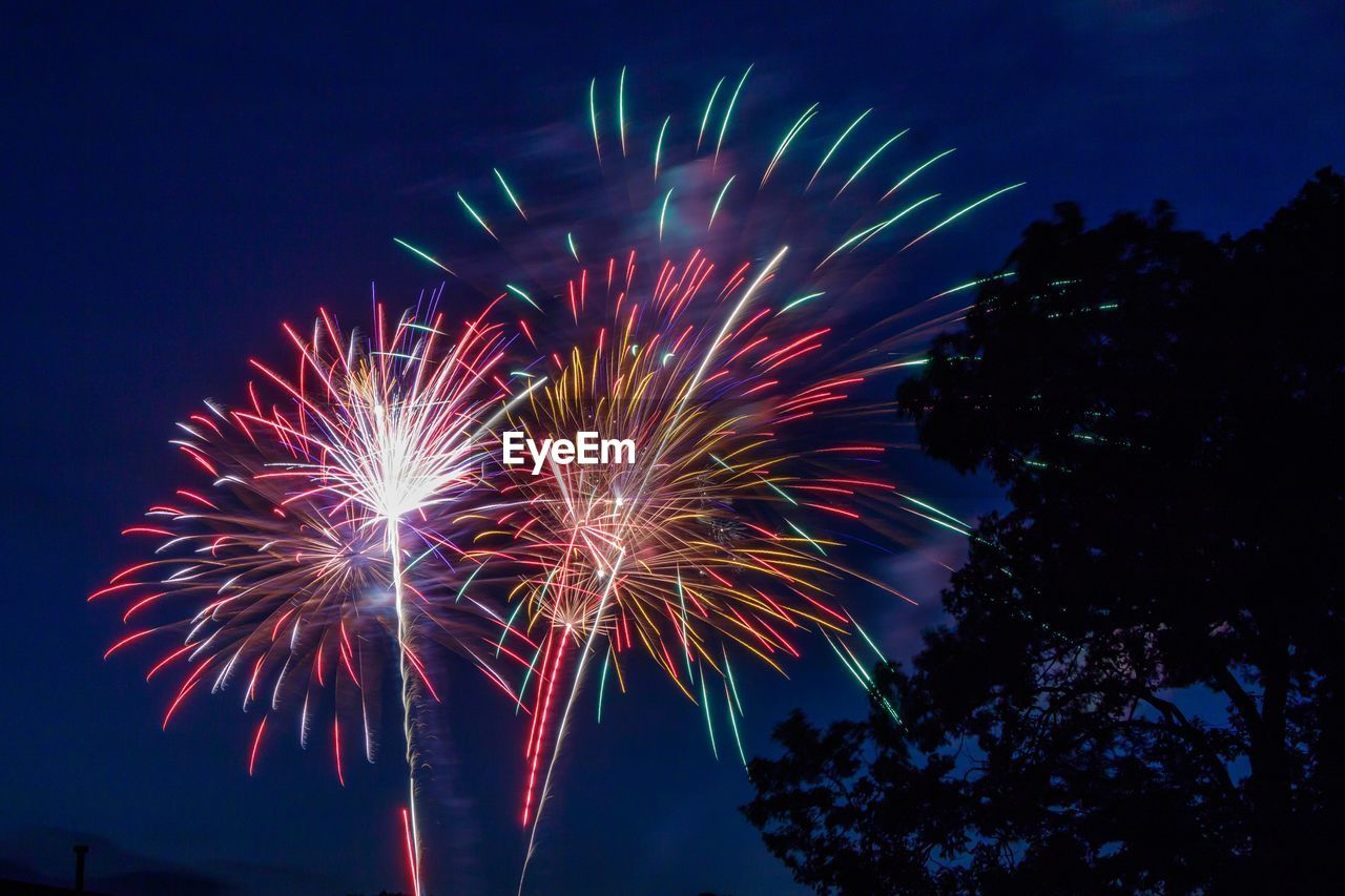 firework display, firework - man made object, celebration, low angle view, night, exploding, long exposure, event, sky, arts culture and entertainment, smoke - physical structure, multi colored, illuminated, outdoors, no people, motion, firework