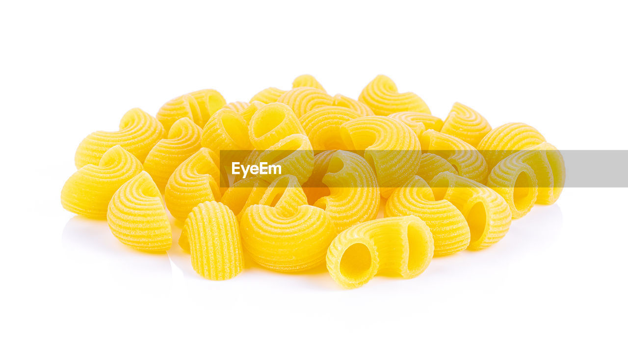 white background, still life, yellow, studio shot, pasta, indoors, italian food, no people, close-up, cut out, freshness, raw food, food, large group of objects, food and drink, pattern, spiral, rolled up, copy space, group of objects, snack