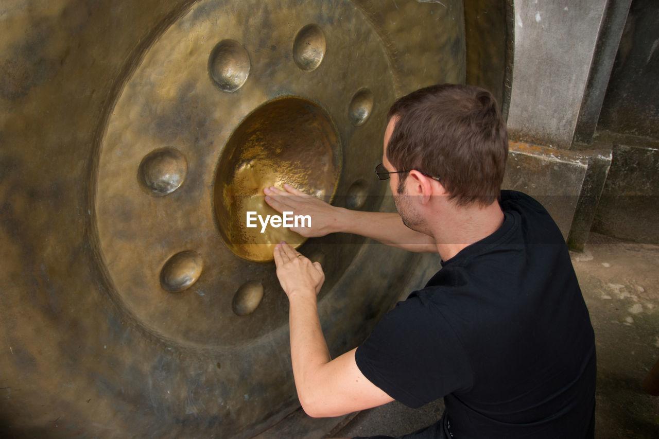 Mid adult man polishing metal in workshop