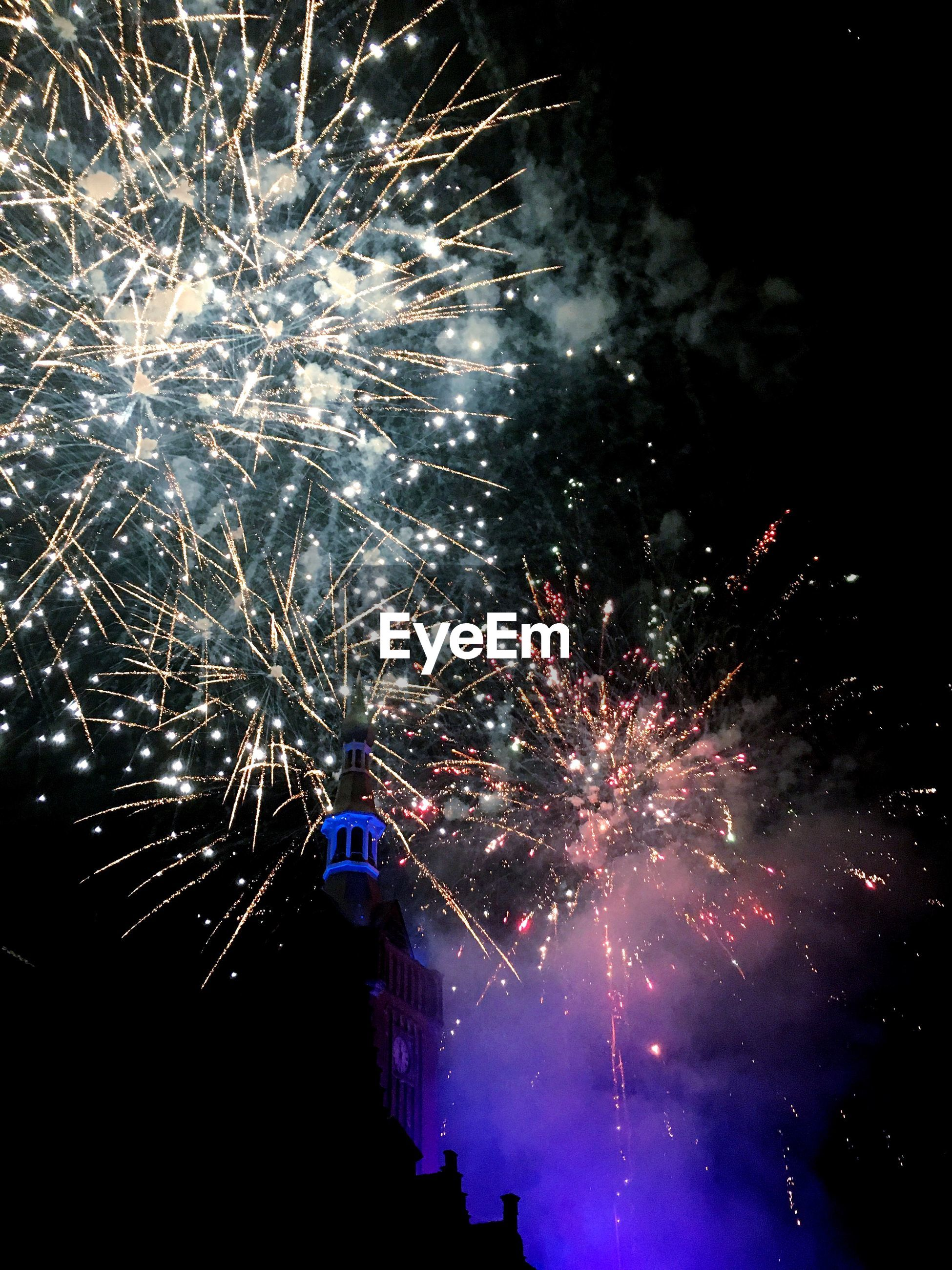 firework display, celebration, exploding, firework - man made object, night, arts culture and entertainment, long exposure, event, sparks, low angle view, glowing, illuminated, multi colored, smoke - physical structure, firework, blurred motion, motion, sky, outdoors, celebration event, no people