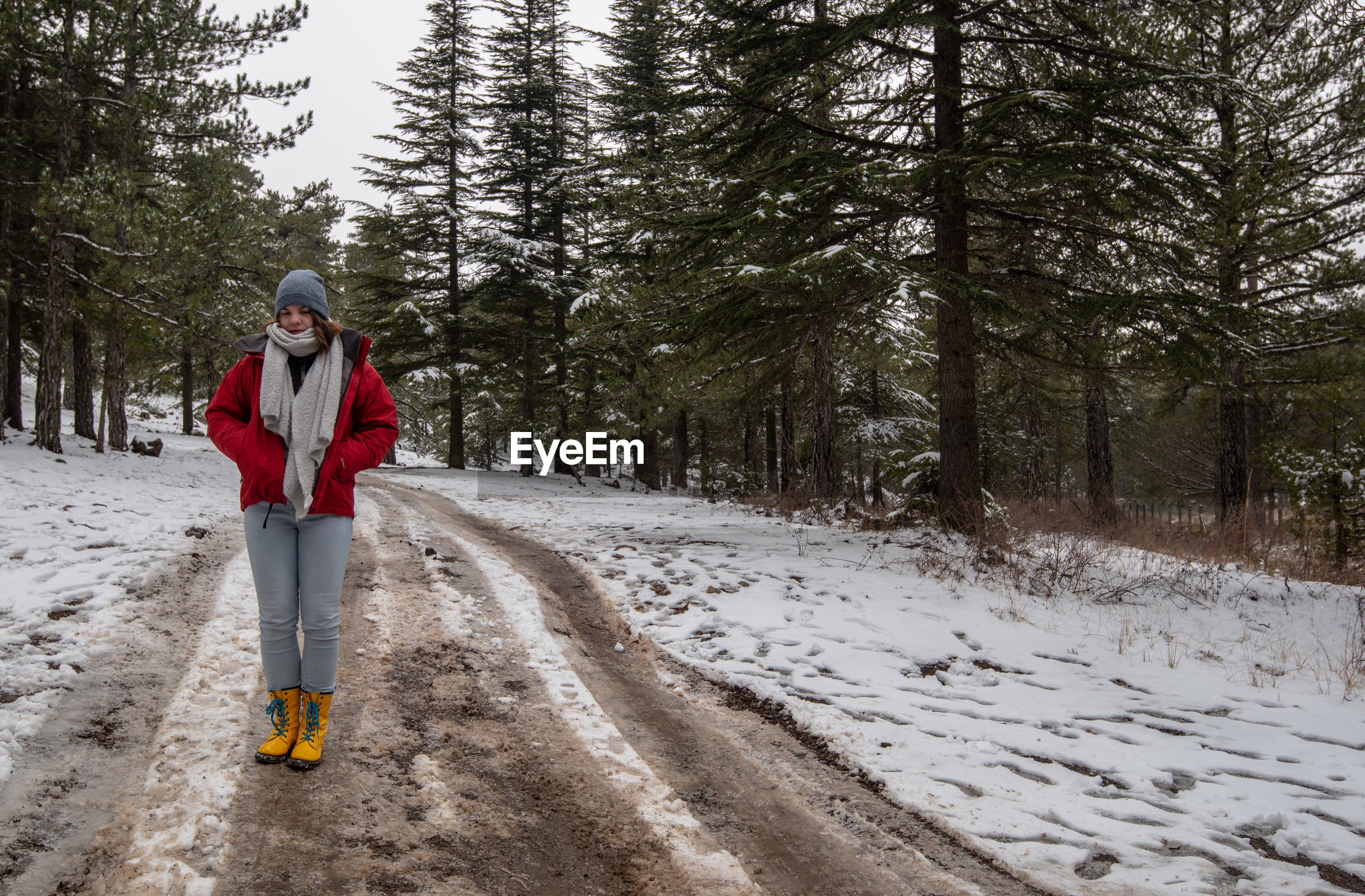 Full length of woman standing on snow covered field against trees in forest