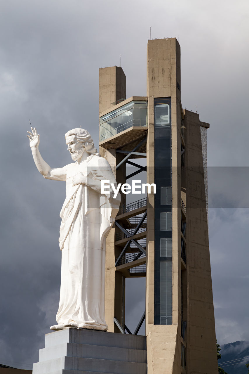 statue, human representation, sculpture, sky, low angle view, female likeness, male likeness, architecture, cloud - sky, travel destinations, built structure, outdoors, no people, day, building exterior