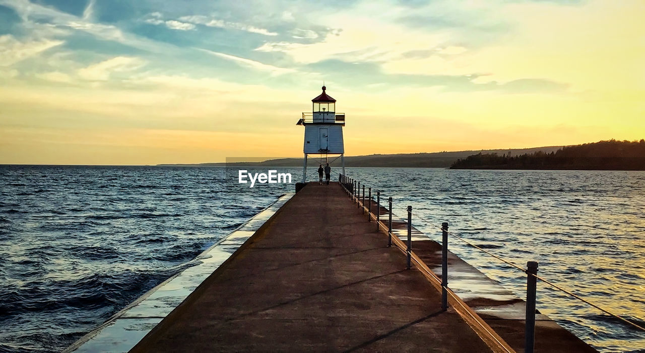 People standing by lighthouse on pier at lake superior against sky