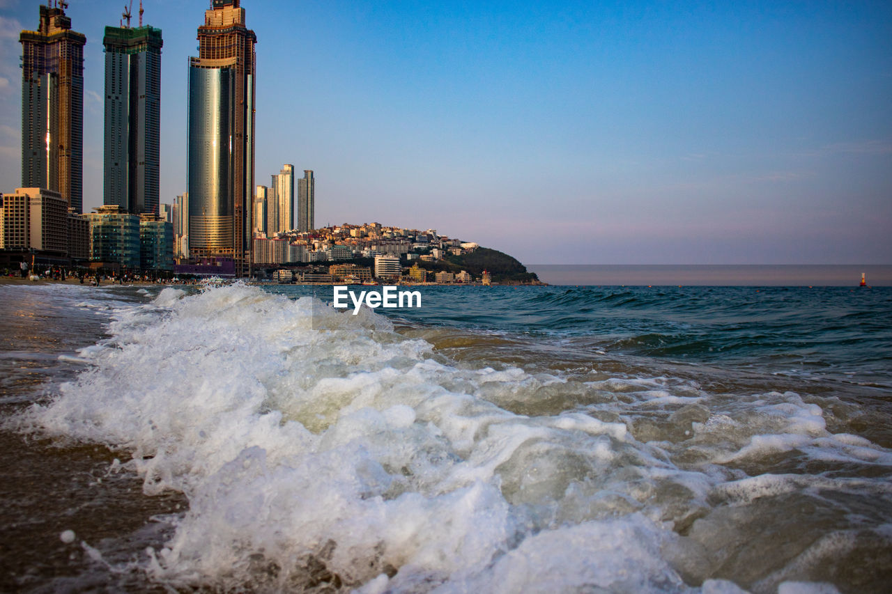 sea, water, sky, motion, architecture, built structure, building exterior, sport, wave, aquatic sport, nature, beach, surfing, beauty in nature, land, building, city, horizon over water, waterfront, outdoors, skyscraper, office building exterior, power in nature