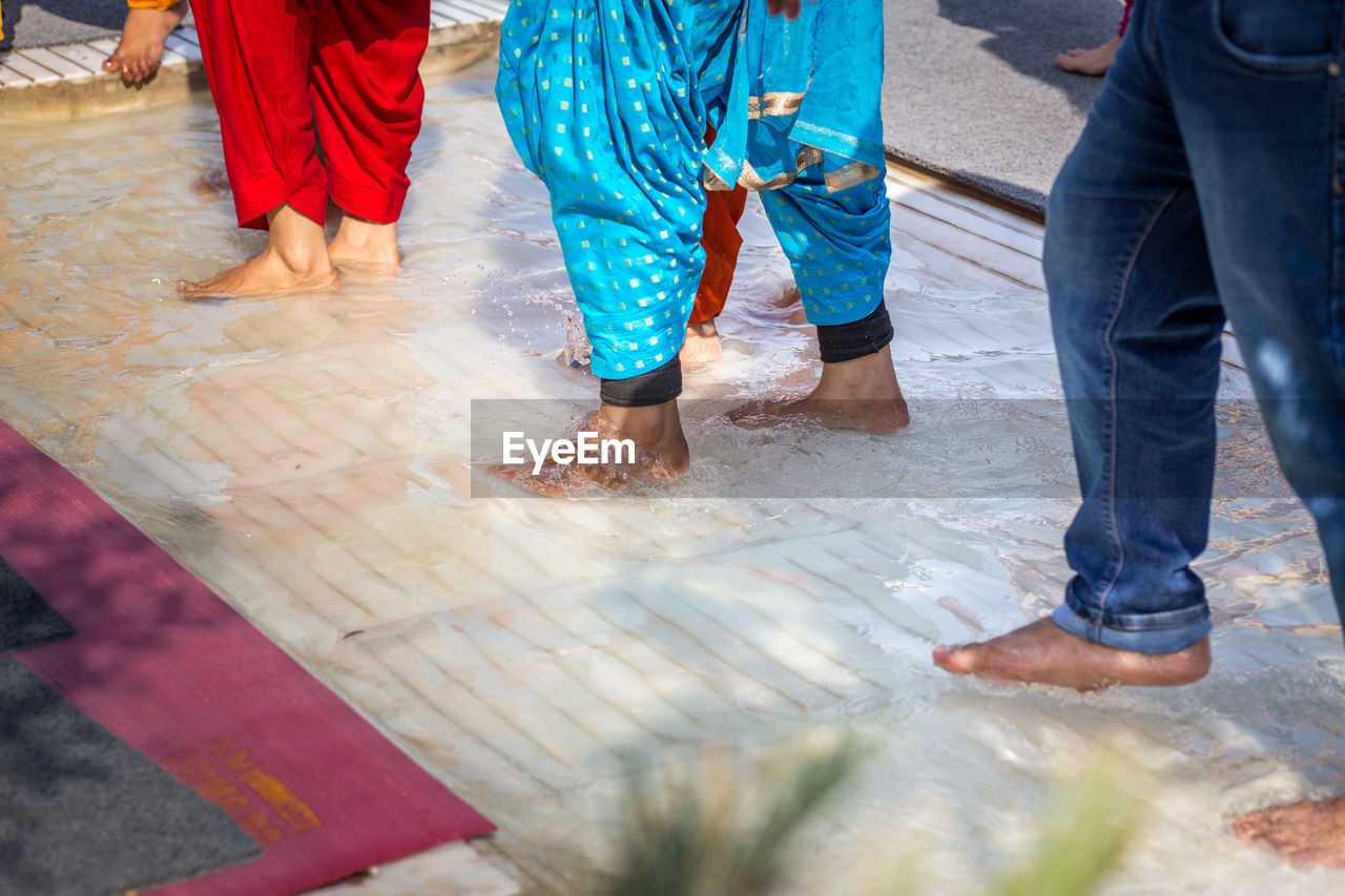 Low section of people cleaning feet outside golden temple