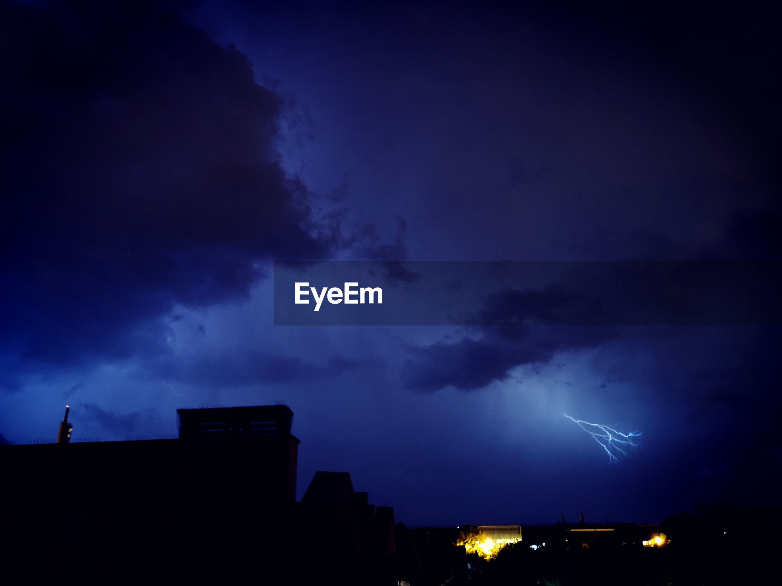 LOW ANGLE VIEW OF LIGHTNING OVER BUILDINGS AGAINST SKY