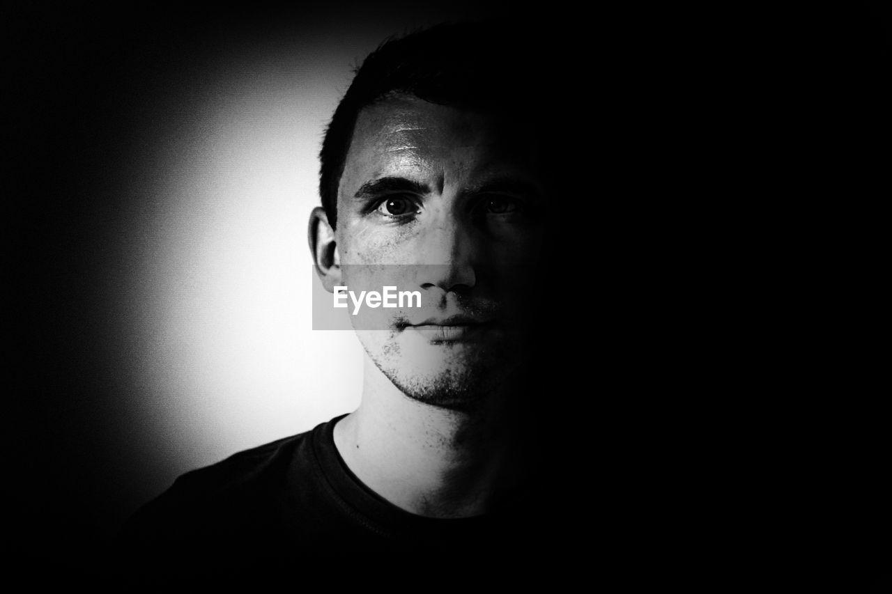 Portrait of man against in darkroom