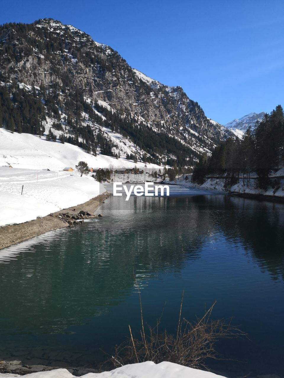 water, mountain, lake, scenics - nature, beauty in nature, tranquility, sky, tranquil scene, cold temperature, nature, day, winter, no people, reflection, snow, non-urban scene, plant, environment, outdoors, snowcapped mountain