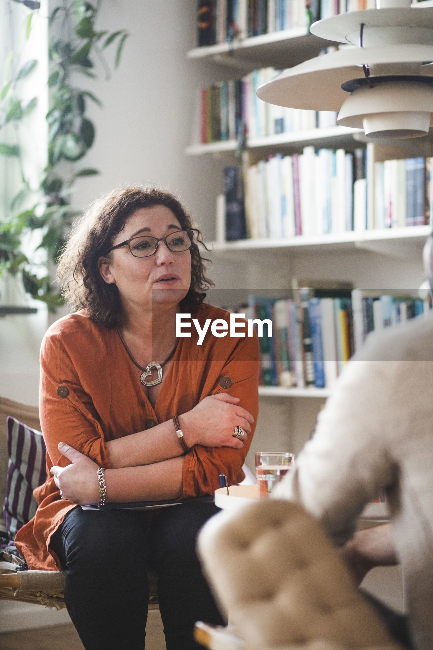 Mature female therapist talking to patient at home office