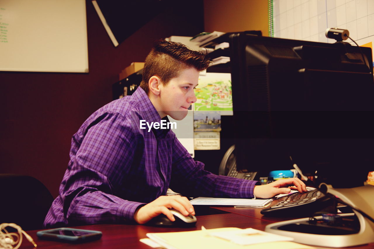 Side View Of Young Woman On Computer At Desk In Office