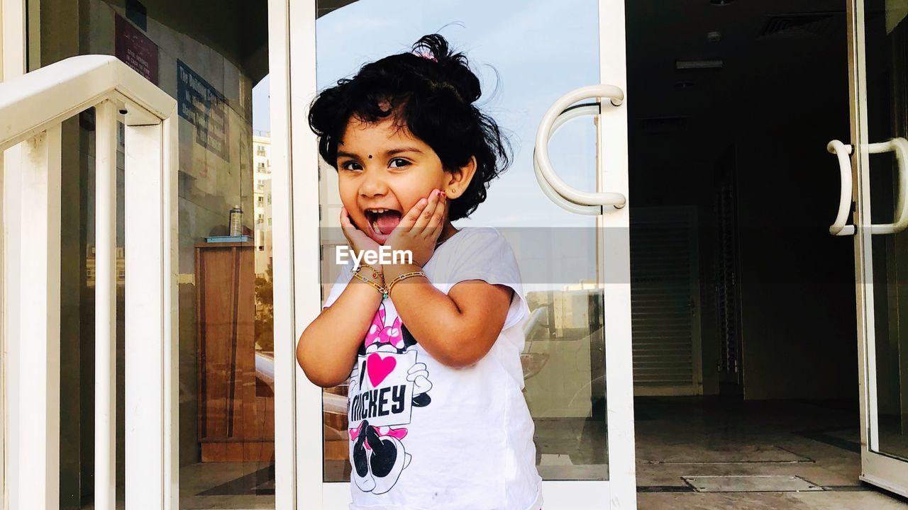 Portrait of smiling girl standing against glass door