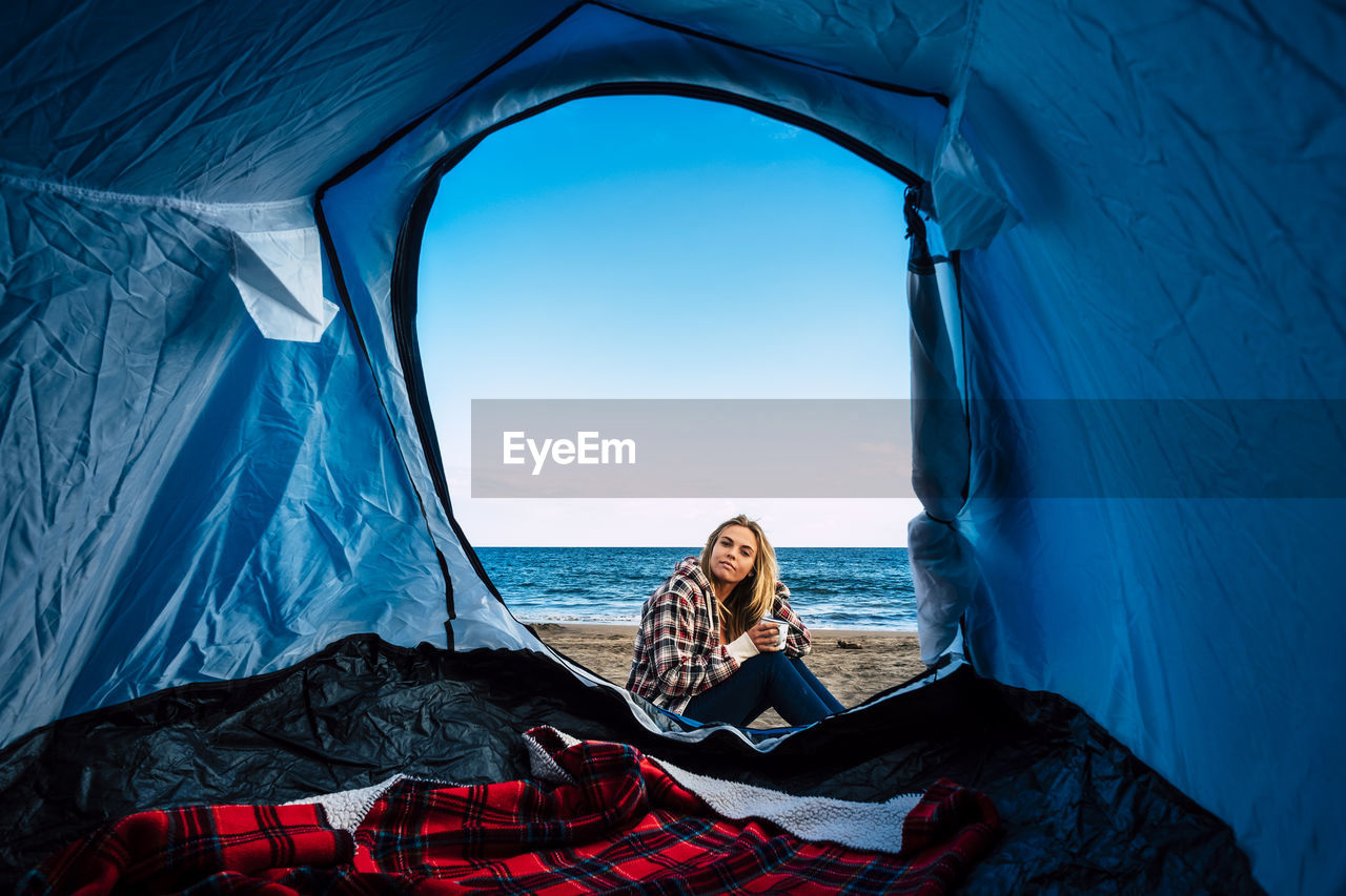 Portrait Of Woman Sitting By Tent At Beach Against Sky