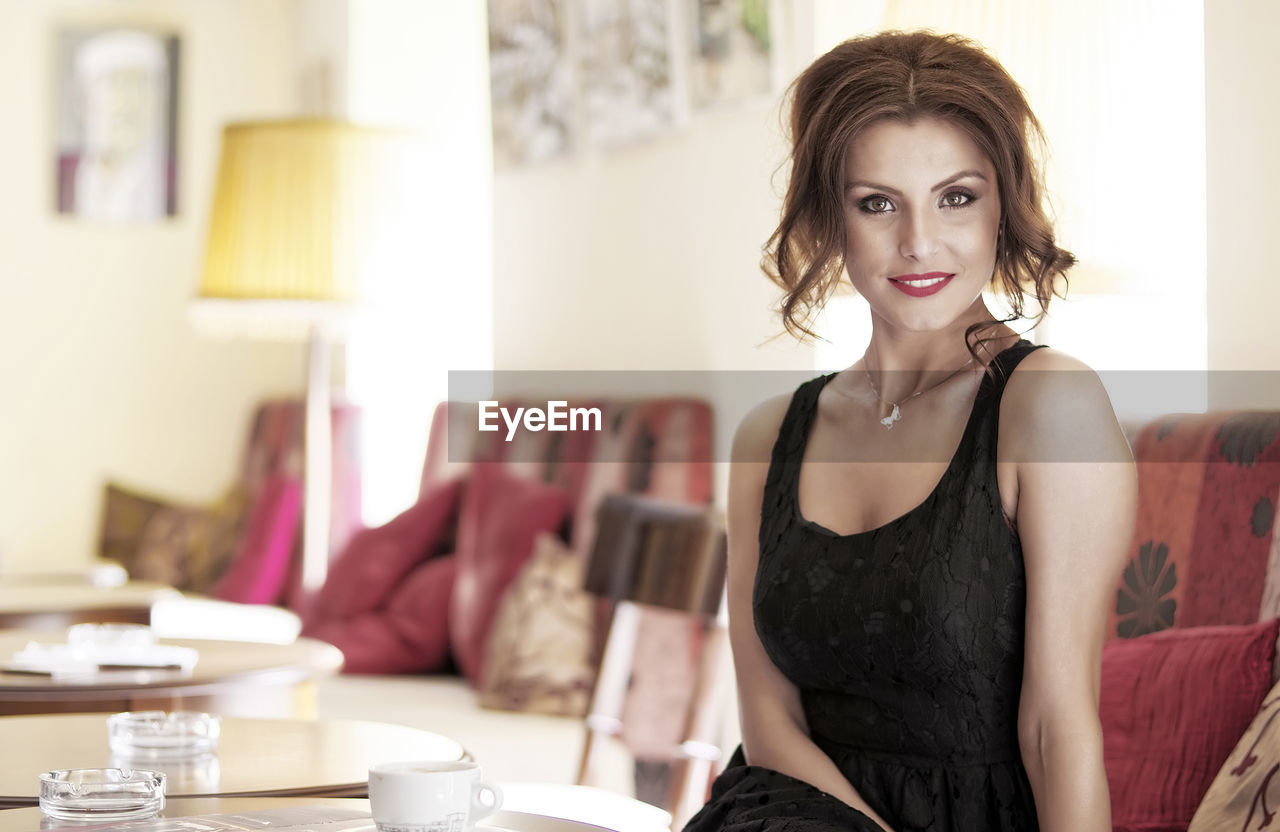 one person, young adult, beautiful woman, focus on foreground, looking at camera, indoors, table, real people, portrait, young women, front view, fashion, sitting, day