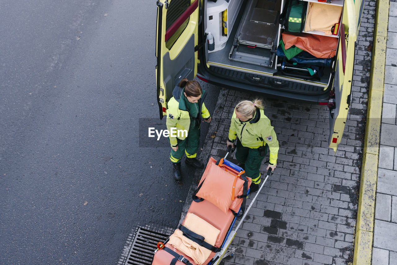 High angle view of female paramedic standing with colleague pushing stretcher outside ambulance on road
