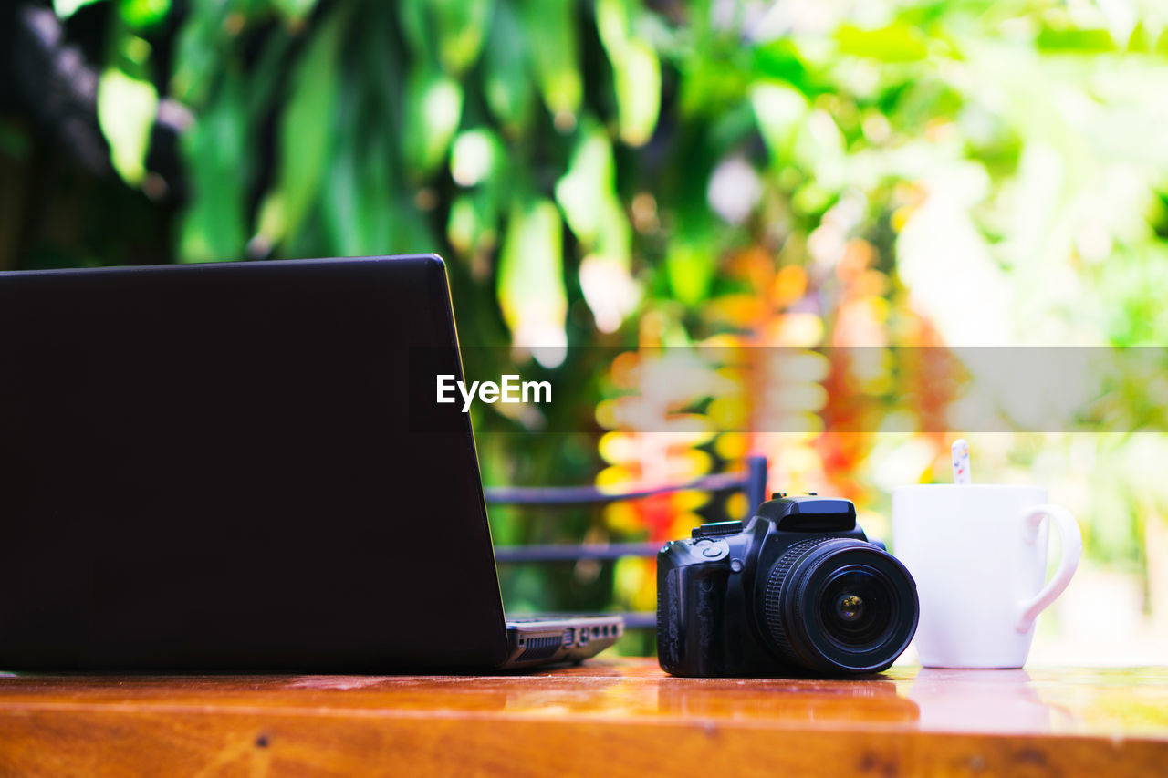 CLOSE-UP OF CAMERA ON TABLE AGAINST BLURRED BACKGROUND