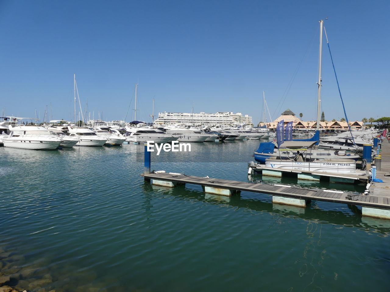 nautical vessel, water, transportation, mode of transportation, moored, sky, sailboat, sea, pole, clear sky, nature, mast, day, harbor, waterfront, no people, blue, sunlight, reflection, yacht, outdoors, marina, anchored, bay
