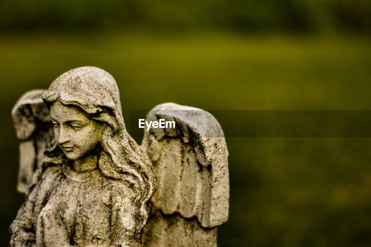sculpture, representation, statue, art and craft, human representation, focus on foreground, no people, creativity, close-up, day, cemetery, craft, grave, religion, male likeness, old, stone material, stone, solid, outdoors, angel