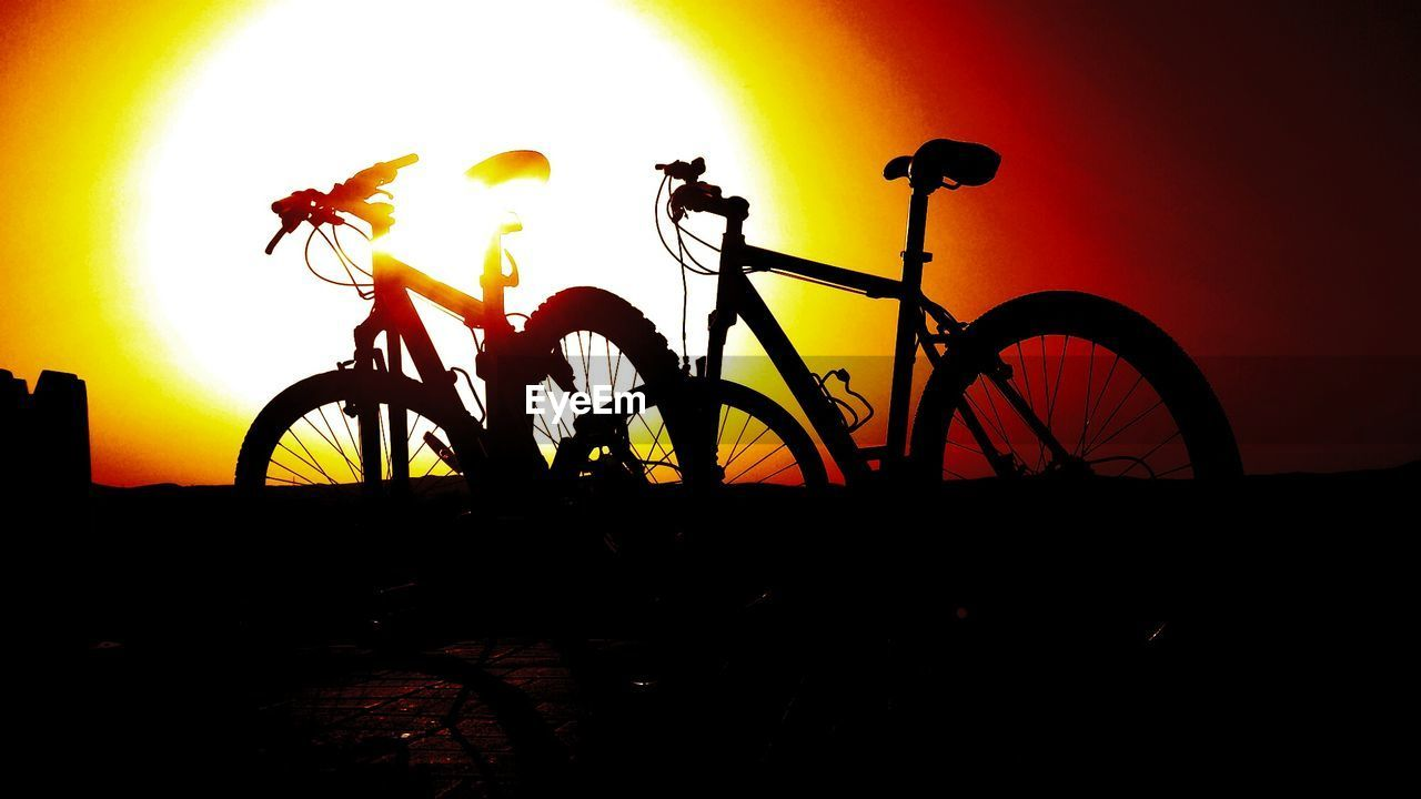 Silhouette bicycles parked at sunset