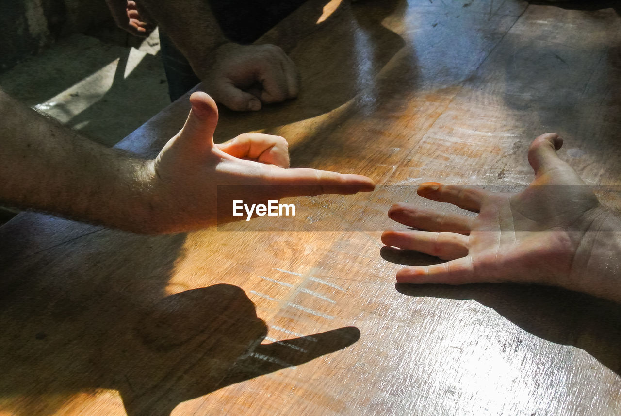 Cropped Hands Of Friends Playing Rock Paper Scissors On Table
