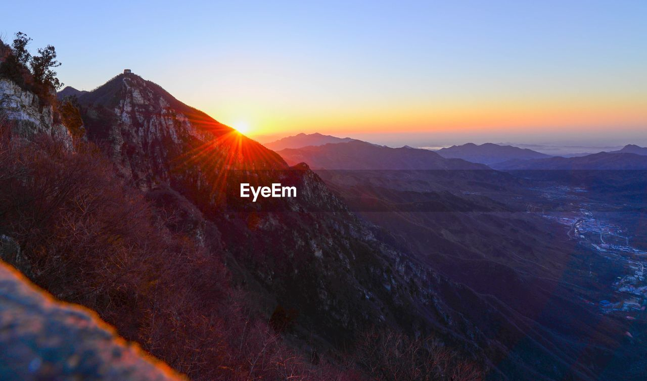 SCENIC VIEW OF MOUNTAINS AGAINST SUNSET SKY