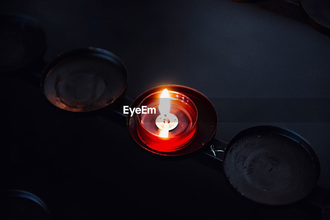 illuminated, burning, flame, fire, candle, heat - temperature, glowing, fire - natural phenomenon, indoors, high angle view, no people, lighting equipment, dark, close-up, directly above, circle, light - natural phenomenon, geometric shape, darkroom, tea light, electric lamp
