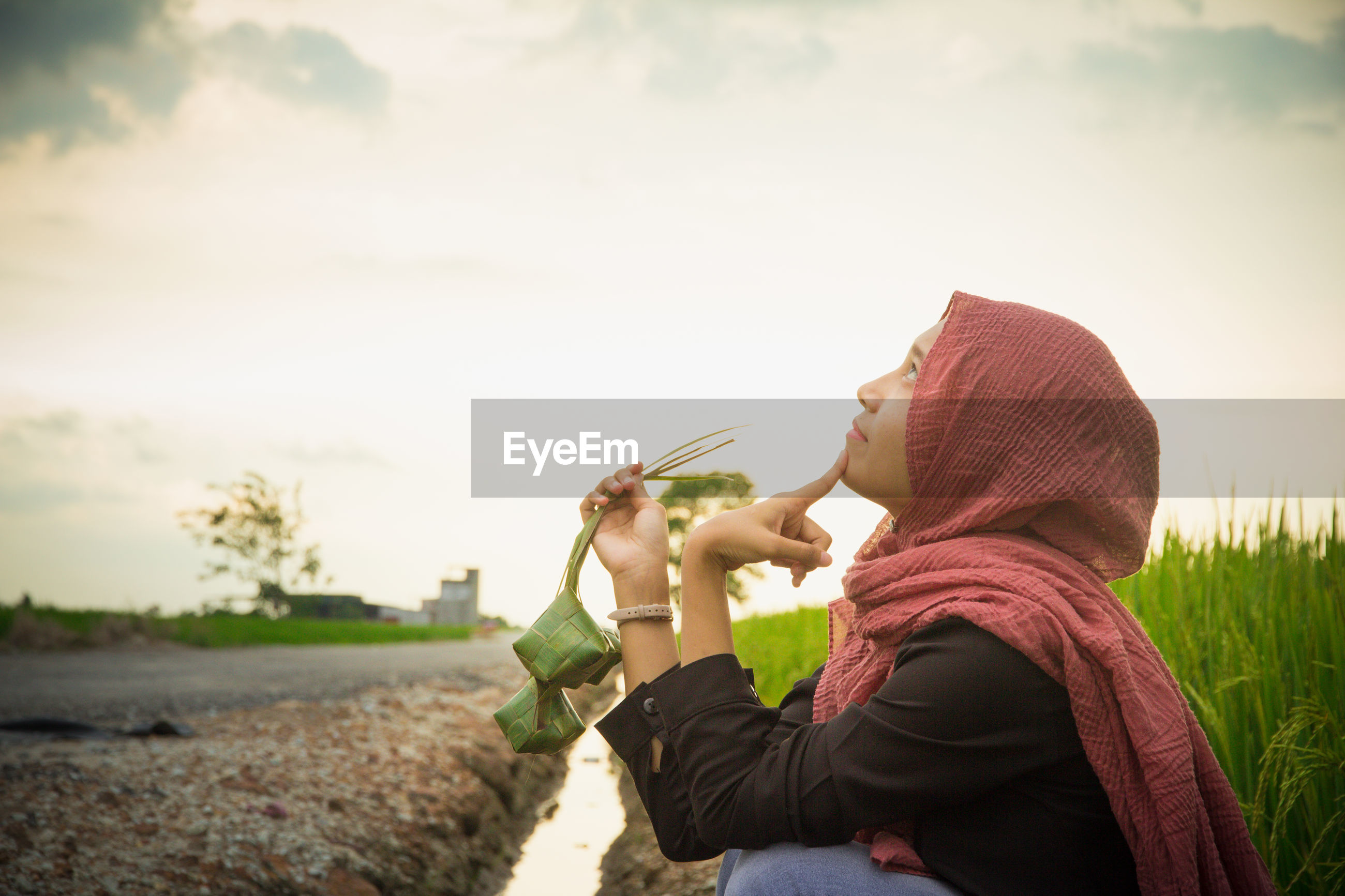 Young woman wearing hijab looking away against sky