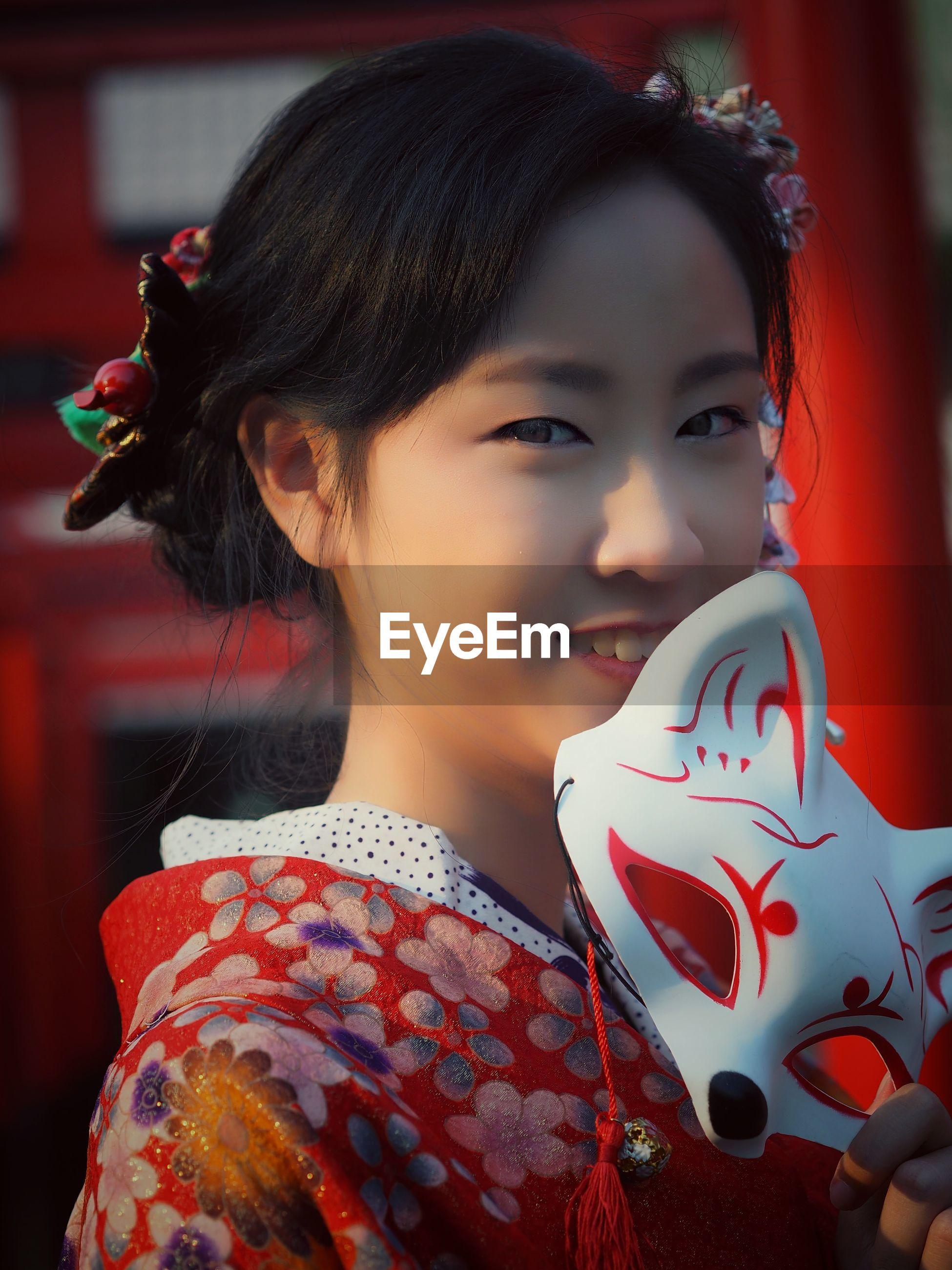Smiling teenage girl wearing kimono outdoors