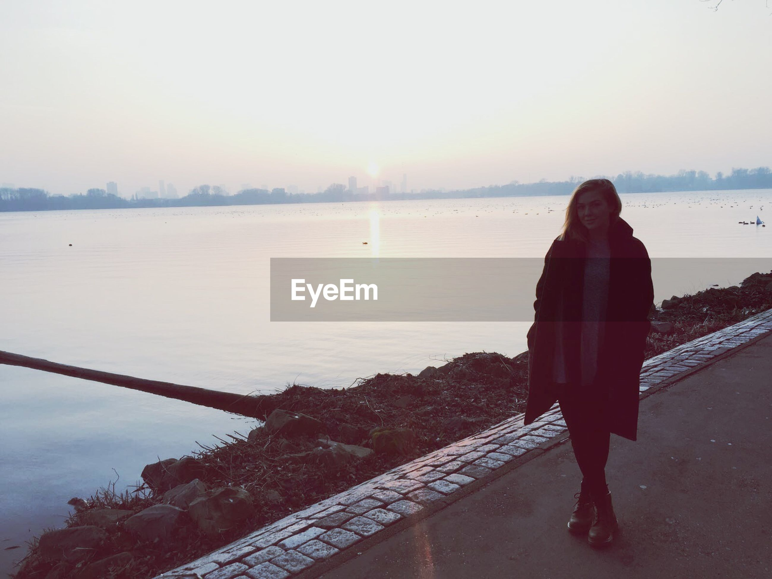 one person, one woman only, only women, water, nature, adults only, full length, leisure activity, beauty in nature, rear view, people, outdoors, women, tranquility, adult, lake, warm clothing, day, young adult