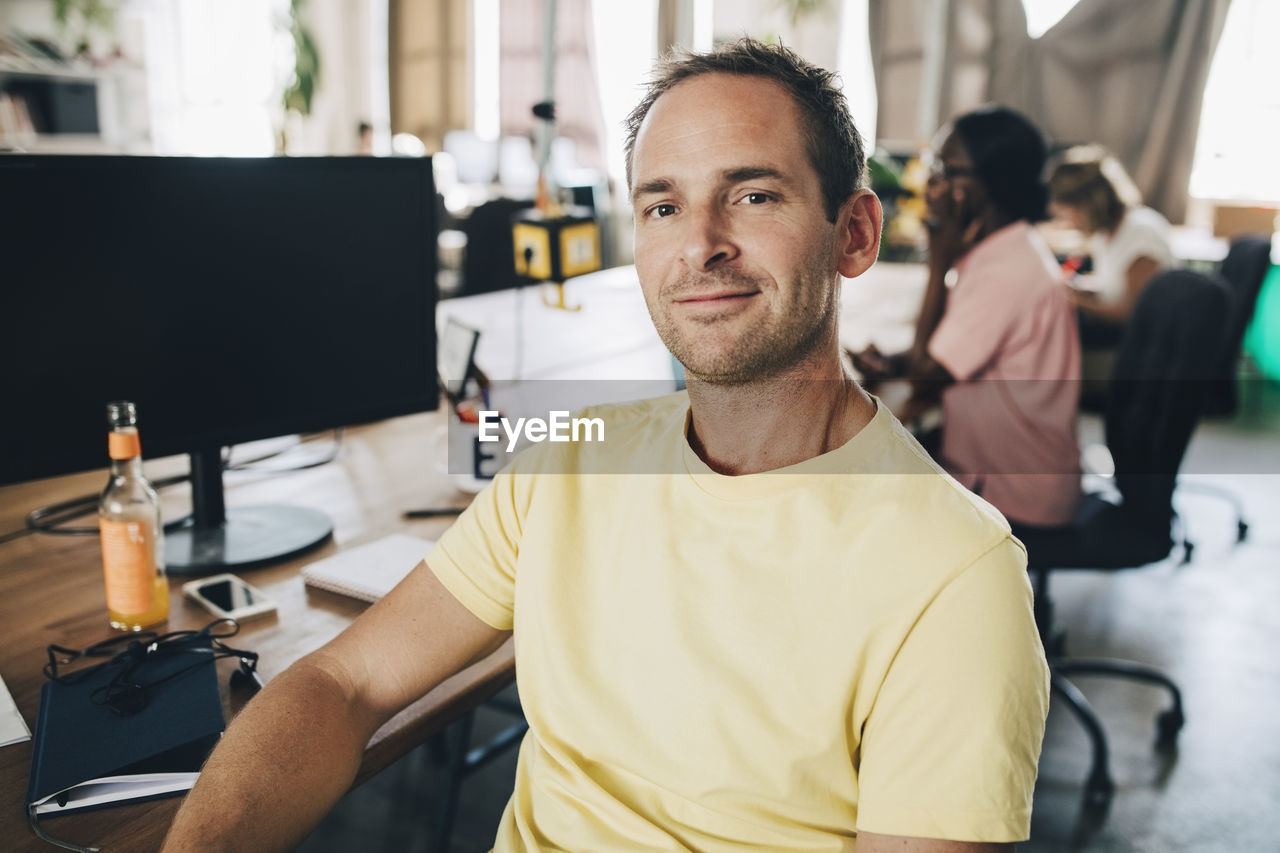 looking at camera, portrait, sitting, office, business, men, one person, table, indoors, furniture, business person, casual clothing, focus on foreground, computer, real people, incidental people, young men, desk, males, mature men