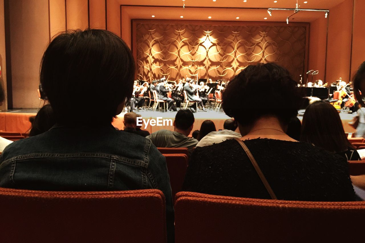 rear view, real people, indoors, men, lifestyles, leisure activity, women, illuminated, large group of people, togetherness, day, people