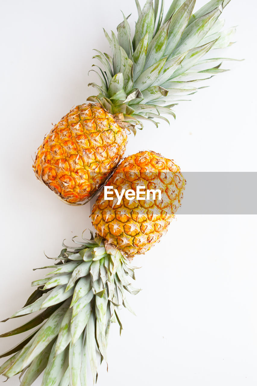 food and drink, studio shot, healthy eating, food, fruit, freshness, white background, indoors, wellbeing, still life, tropical fruit, pineapple, no people, green color, close-up, orange color, leaf, plant part, table, plant, lychee, ripe