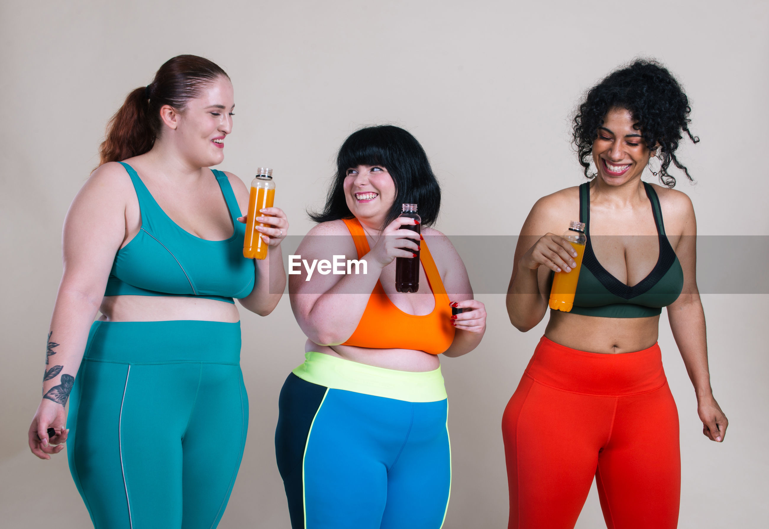 Smiling friends holding drink against colored background