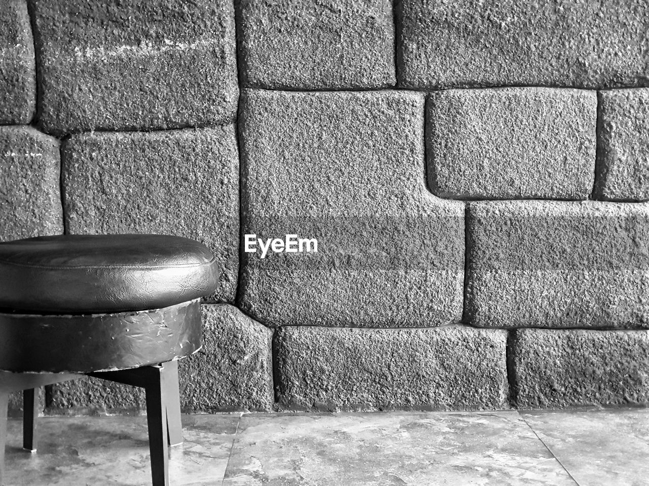wall - building feature, seat, absence, chair, wall, no people, built structure, architecture, brick, empty, furniture, indoors, brick wall, day, table, still life, sunlight, stone wall, flooring, stool
