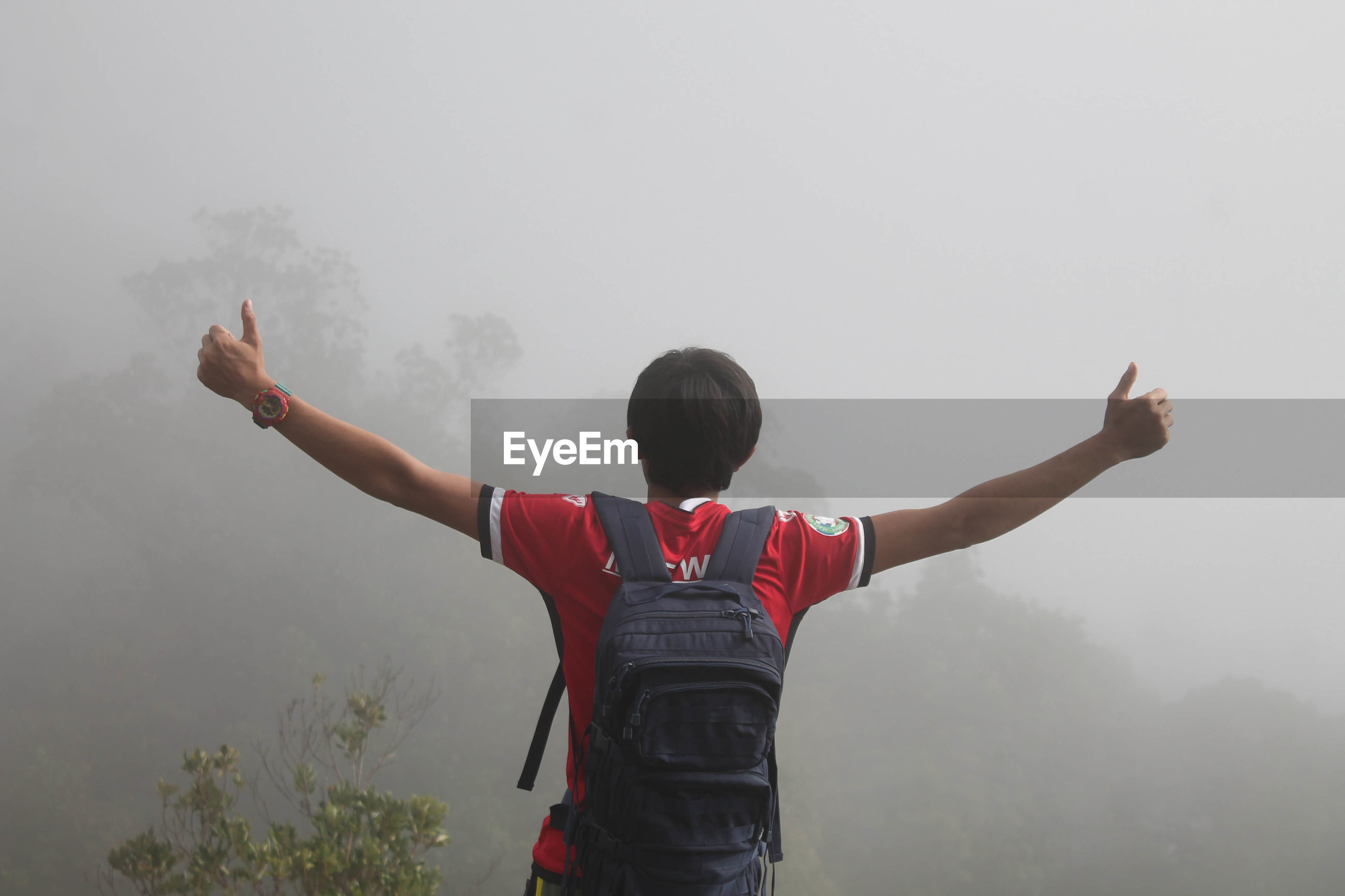 Rear view of man with arms outstretched standing in foggy weather