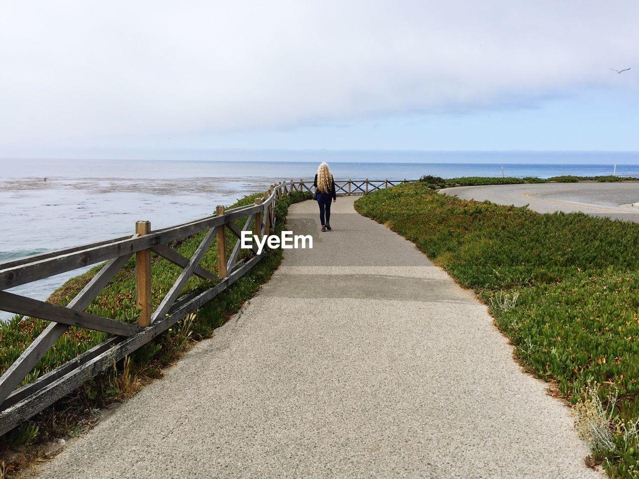 Rear View Of Woman Walking On Promenade By Sea Against Sky