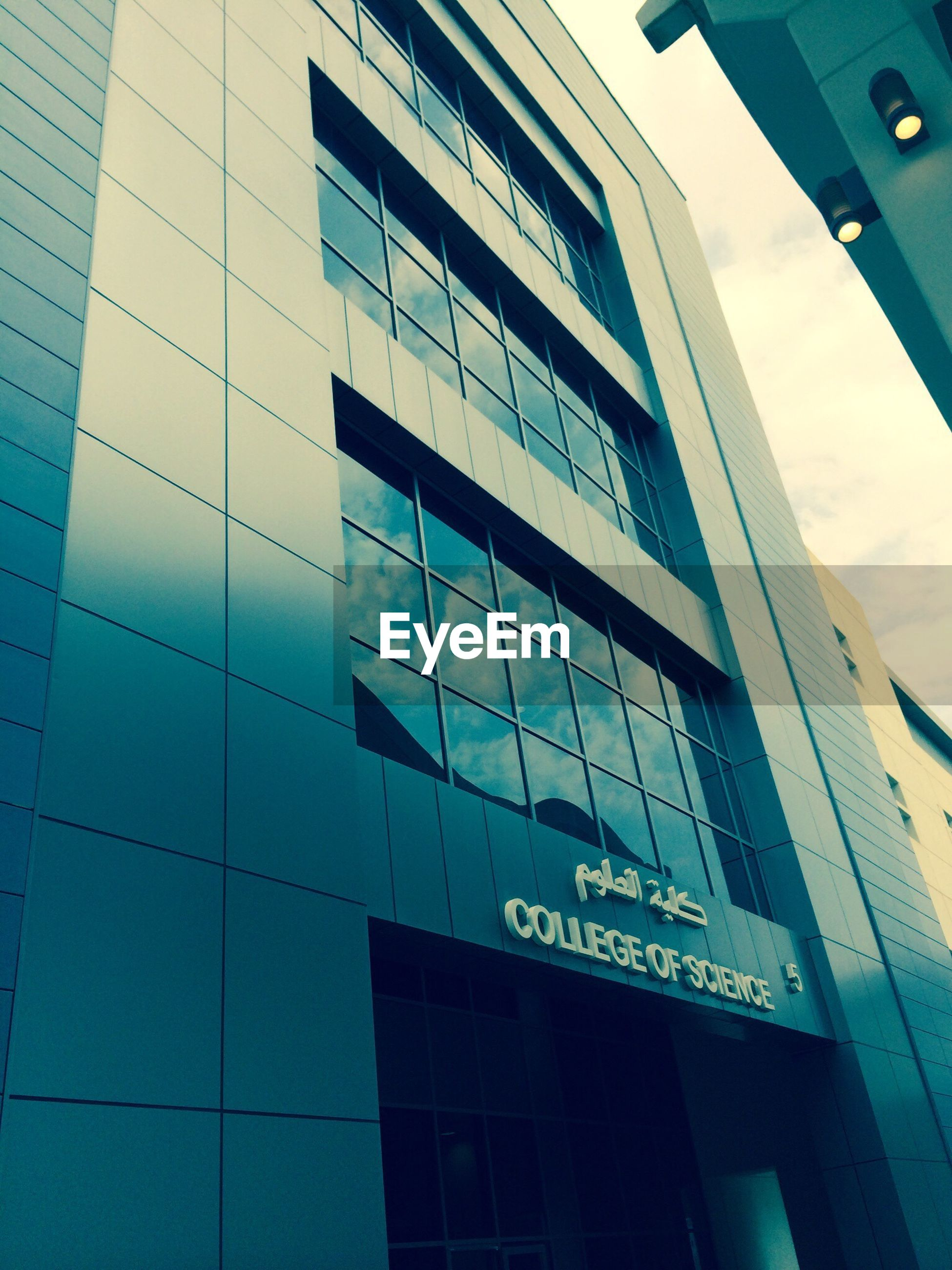 architecture, building exterior, low angle view, built structure, modern, office building, city, building, glass - material, window, reflection, text, communication, western script, skyscraper, sky, day, tall - high, city life, tower